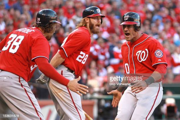 Michael Morse Jayson Werth and Ian Desmond of the Washington Nationals celebrate after Morse and Desmond score the tying and go ahead runs in the...