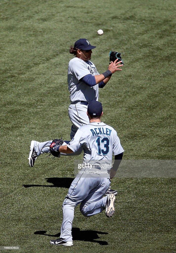 Michael Morse #38 of the Seattle Mariners cannot get to a double hit in the seventh inning as Dustin Ackley #13 watches during MLB game action by Henry Blanco #22 of the Toronto Blue Jays on May 4, 2013 at Rogers Centre in Toronto, Ontario, Canada.
