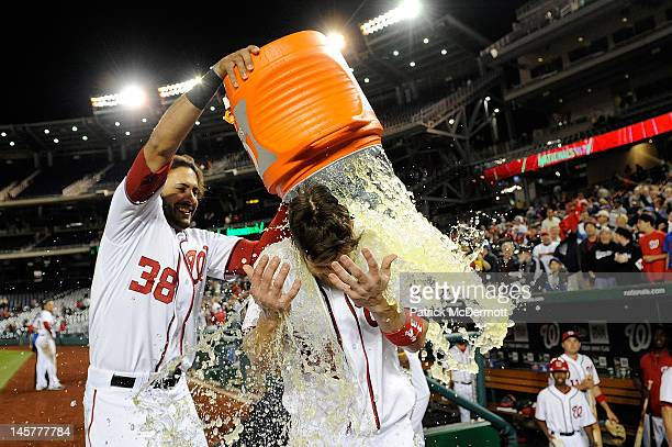 Michael Morse of the Washington Nationals dumps Gatorade on Bryce Harper after he hit the game winning RBI single in the twelfth inning against the...