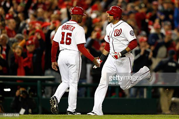 Michael Morse of the Washington Nationals rounds the bases and is congratulated by third base coach Bo Porter after Morse hits a tworun home run in...