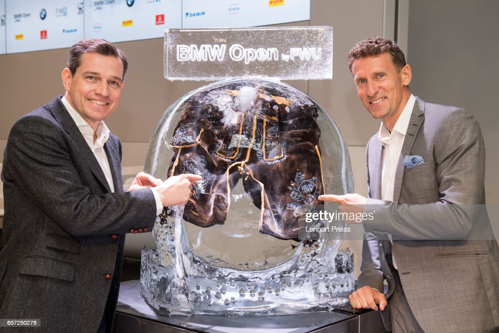 Michael Mronz (L), promoter of the BMW Open tennis tournament, and Patrik Kuehnen, BMW Open tournament director, pose next to a traditional Bavarian Lederhose, frozen in an ice sculpture of a tennis ball, after the BMW Open press conference on March 24, 2017 in Munich, Germany.