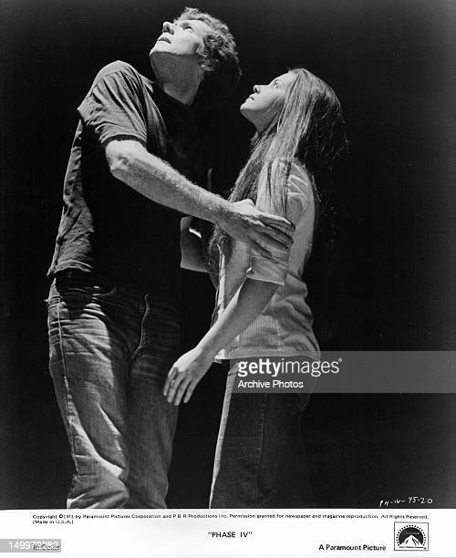 Michael Murphy holding Lynne Frederick while looking up in a scene from the film 'Phase IV' 1974