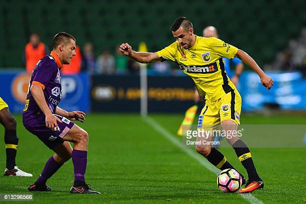 Michael Neill of the Central Coast Mariners holds the ball in front of Chris Harold of the Perth Glory during the round one ALeague match between the...