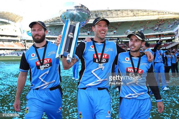 Michael Neser Ben Laughlin and Jonathan Wells of the Strikers walk a lap of honour with the trophy after winning the Big Bash League Final match...