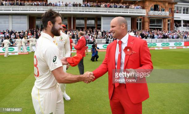 Michael Neser of Australia presents former England captain Andrew Strauss with his red cap ahead of day two of the 2nd Specsavers Ashes Test match at...