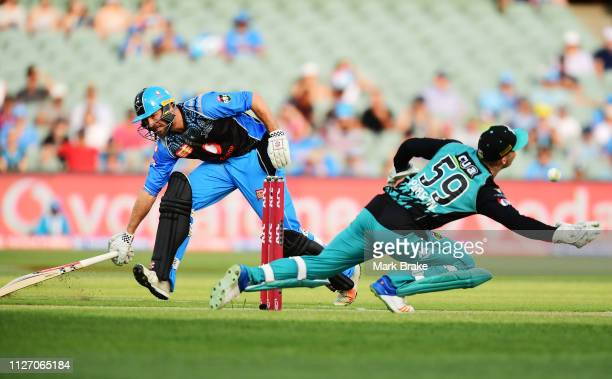Michael Neser of the Adelaide Strikers makes his crease as Jimmy Peirson of the Heat dives for the return throw during the Big Bash League match...