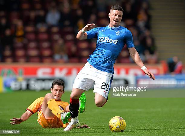 Michael O'Halloran of Rangers is tackled by Carl McHugh of Motherwell during the Scottish League Cup First Round Group Stage match between Motherwell...