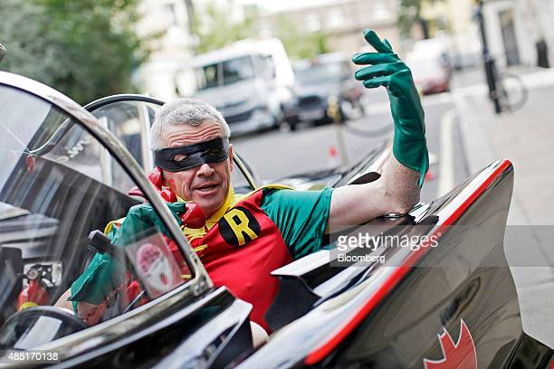 Michael O'Leary chief executive officer of Ryanair Holdings Plc dressed as superhero sidekick Robin poses for a photograph in a replica Batmobile...