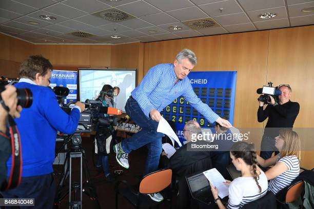 Michael O'Leary chief executive officer of Ryanair Holdings Plc hands out press releases to journalists during a news conference at Tegel airport in...