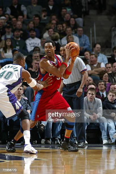 Michael Olowokandi of the Los Angeles Clippers looks to pass against Ervin Johnson of the Milwaukee Bucks during the first quarter of an NBA game at...