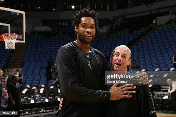 Michael Olowokandi of the Minnesota Timberwolves poses for a picture with David Miller assistant coach of the New Orleans/Oklahoma City Hornets on...
