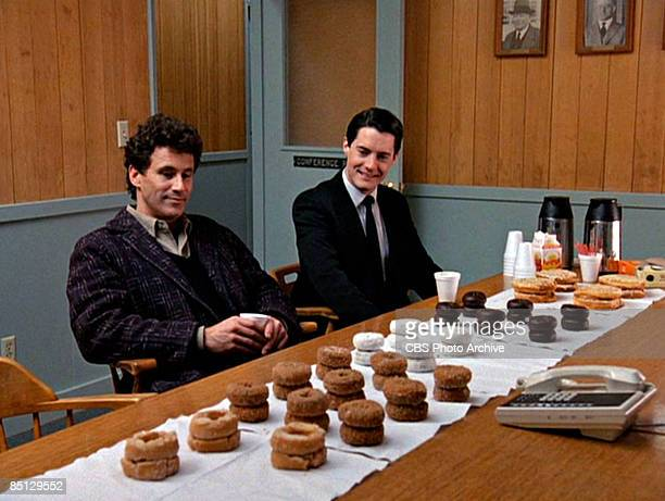 Michael Ontkean as Sheriff Harry S Truman and Kyle MacLachlan as Special Agent Dale Cooper eye donuts arrayed on a table in a scene from the pilot...