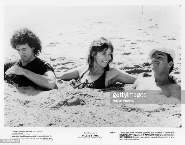 Michael Ontkean Margot Kidder and Ray Sharkey are buried in the sand in a scene from the 20th Century Fox movie Willie Phil circa 1980