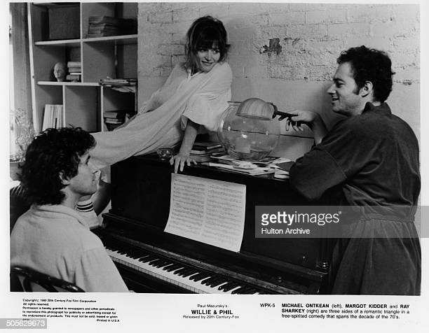Michael Ontkean Margot Kidder and Ray Sharkey talk over a piano in a scene from the 20th Century Fox movie Willie Phil circa 1980