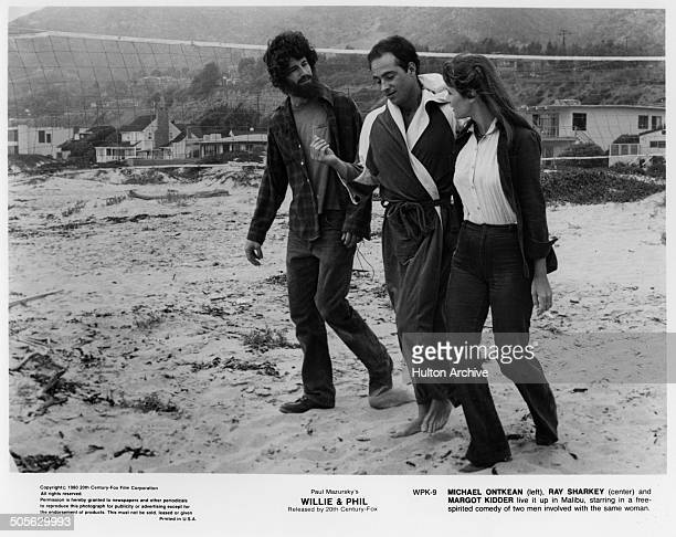 Michael Ontkean Ray Sharkey and Margot Kidder walk on the beach in a scene from the 20th Century Fox movie Willie Phil circa 1980