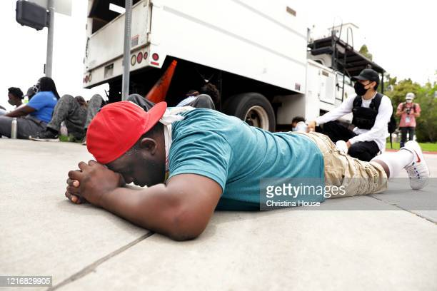 Michael O'Quinn of Compton prays during a peaceful protest where demonstrators laid down to approximate the time that George Floyd was on the ground...