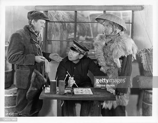 Michael O'Shea talking to an unknown actor that is writing kanji on a sheet of paper in a scene from the film 'Jack London' 1943