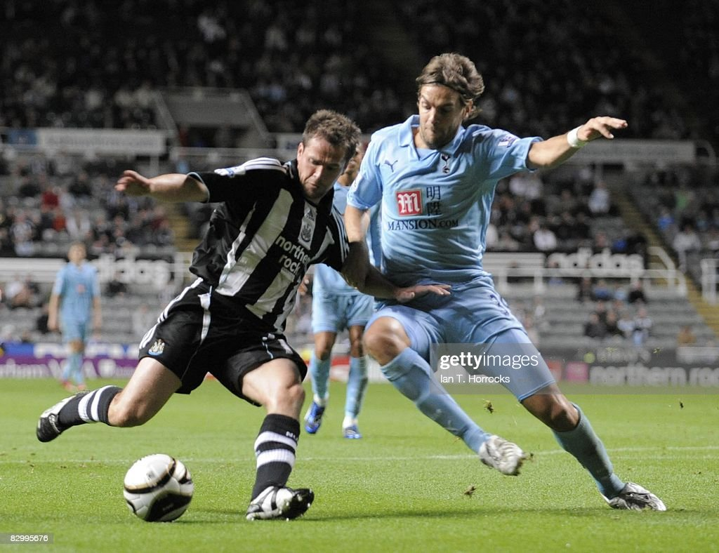 Michael Owen (L) of Newcastle United is challenged by Jonathan Woodgate of Tottenham Hotspur during the Carling Cup Third Round match between Newcastle United and Tottenham Hotspur at St James' Park on September 24, 2008 in Newcastle, England.