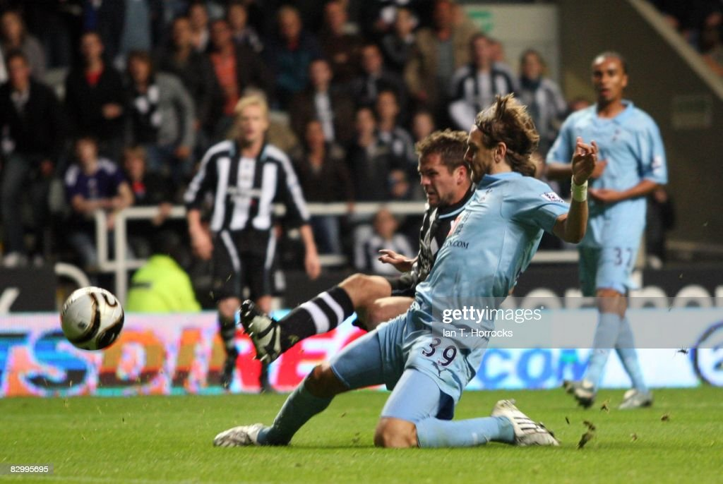 Michael Owen of Newcastle United shoots past Jonathan Woodgate of Tottenham Hotspur during the Carling Cup Third Round match between Newcastle United and Tottenham Hotspur at St James' Park on September 24, 2008 in Newcastle, England.