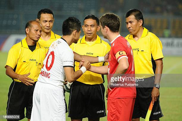Michael Owen shakes hand with Bambang Pamungkas before kick off in the friendly match between Indonesia Red and the Manchester United Legends on...