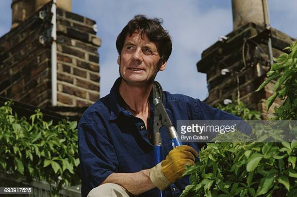 Michael Palin Actor Author and Month Python star holds a pair of Secateurs as he tackles plants growing on his rooftop in his garden in London UK in...