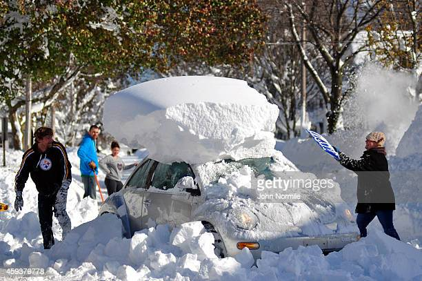 Michael Palmer and Carin Schultz work to clear her car of snow and remove it from Union street on November 20 2014 in the suburb of Hamburg Buffalo...