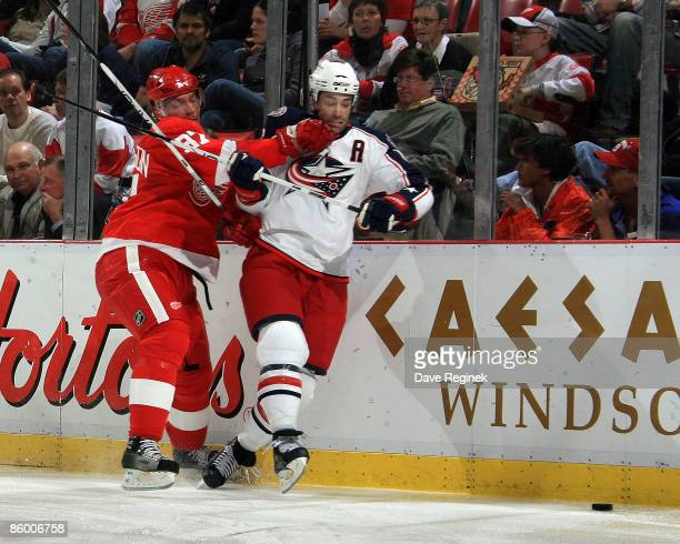 Michael Peca of the Columbus Blue Jackets and Mikael Samuelsson of the Detroit Red Wings battle for the puck in the corner during Game One of the...