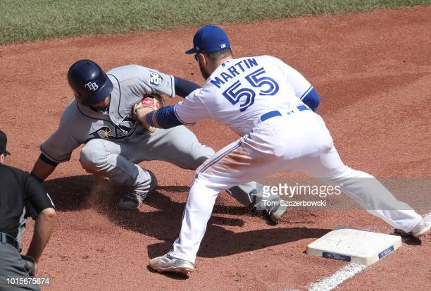 Michael Perez of the Tampa Bay Rays is tagged out by Russell Martin of the Toronto Blue Jays at third base as he tries to advance on a failed...