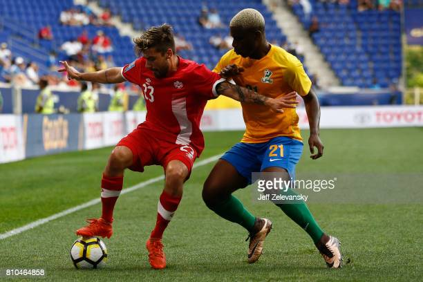 Michael Petrasso of Canada fights for the ball with Schaquille Dutard of French Guiana during their Concacaf Gold Cup match at Red Bull Arena on July...