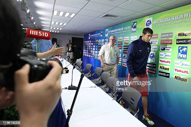 Michael Phelps and coach Bob Bowman of the United States walk out of the room after participating in a press conference on Day Eight of the 14th FINA...