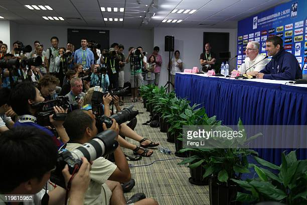 Michael Phelps and coach Eddie Reese of the United States are surrounded by media participate in a press conference on Day Eight of the 14th FINA...
