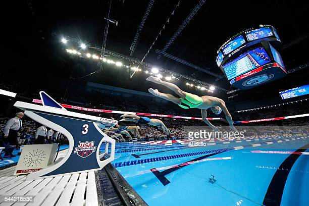 Michael Phelps and Tim Phillips of the United States dive in to compete in a semifinal heat for the Men's 100 Meter Butterfly during Day Six of the...