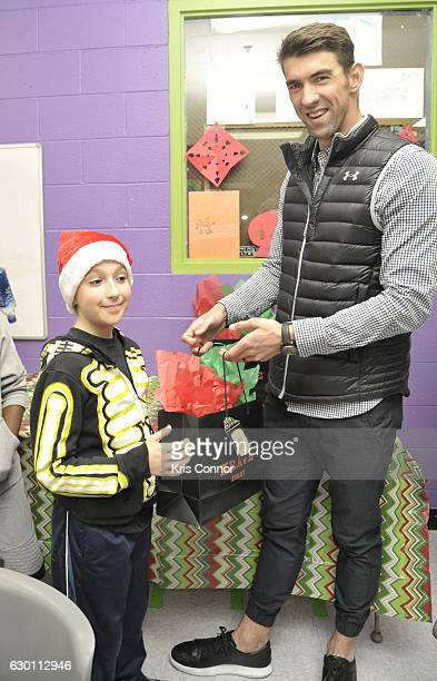 Michael Phelps hands out gift bags to children as he visits the Boys Girls Club of Harford County to present a check for $20000 from the Michael...