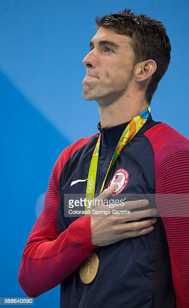 Michael Phelps looks up at the US flag as it's raised during the medal ceremony where he was awarded his 22nd career Olympic gold medal after he won...