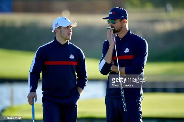 Michael Phelps of Team USA and Nick Jonas of Team USA in discussion during the celebrity challenge match ahead of the 2018 Ryder Cup at Le Golf...