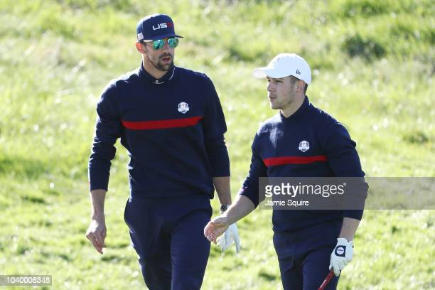 Michael Phelps of Team USA and Nick Jonas of Team USA walk on the fairway during the celebrity challenge match ahead of the 2018 Ryder Cup at Le Golf...