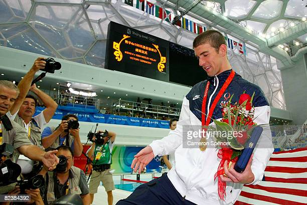 Michael Phelps of the United States makes his way to his family in the stands after receiving his gold medal for the Men's 4x100 Medley Relay at the...