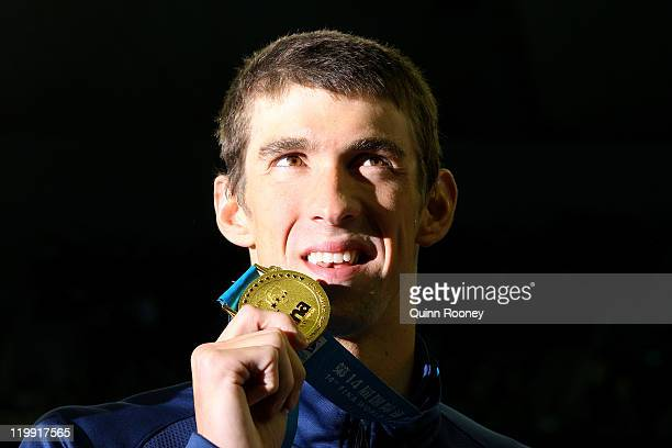 Michael Phelps of the United States poses with his gold medal in the Men's 200m Butterfly Final during Day Twelve of the 14th FINA World...