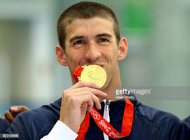 Michael Phelps of the United States poses with the gold medal during the medal ceremony for the Men's 4 x 100m Freestyle Relay held at the National...