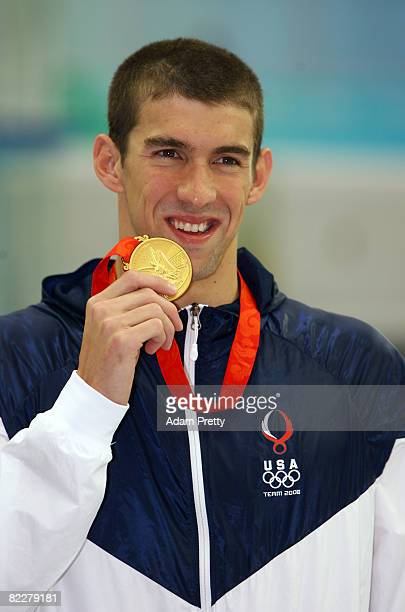 Michael Phelps of the United States poses with the gold medal during the medal ceremony for the Men's 200m Butterfly held at the National Aquatics...