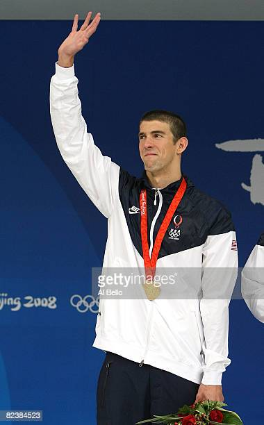 Michael Phelps of the United States waves to the crowd wearing his eighth gold medal during the medal ceremony for the Men's 4x100 Medley Relay at...