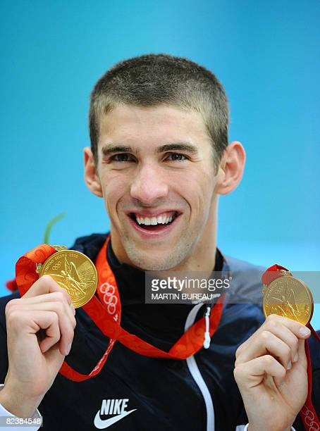 Michael Phelps of the US poses after the men's 4 x 100m medley relay swimming final medal ceremony at the National Aquatics Center during the 2008...