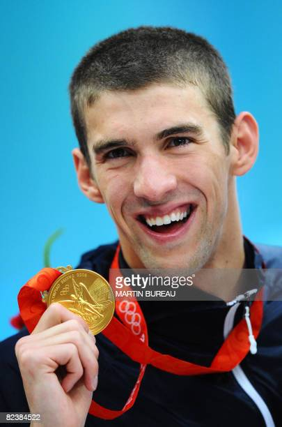 Michael Phelps of the US stands on the podium for the men's 4 x 100m medley relay swimming final medal ceremony at the National Aquatics Center...