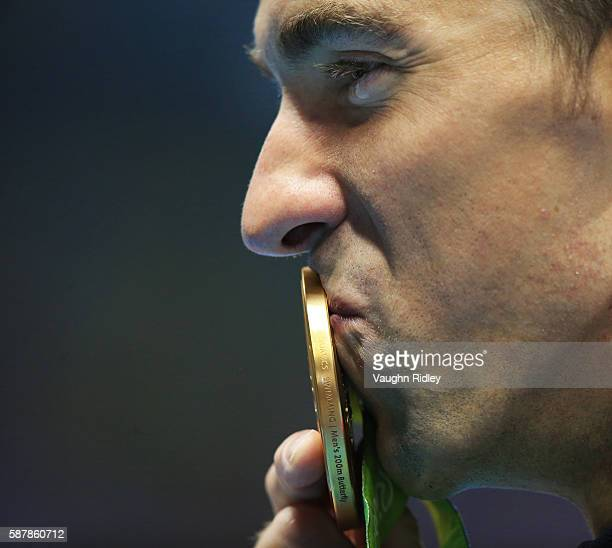 Michael Phelps of the USA kisses his medal with a tear in his eye after winning Gold in the Men's 200m Butterfly Final on Day 4 of the Rio 2016...