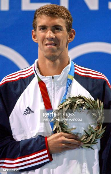 Michael Phelps poses on the podium after winning the men's 200m individual medley final, at the 2004 Olympic Games at the Olympic Aquatic Center in...