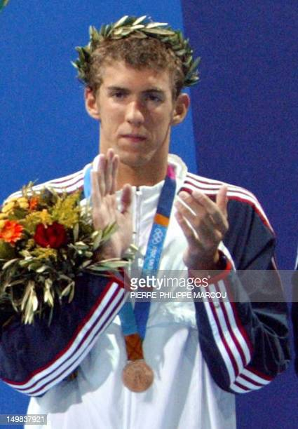 US Michael Phelps reacts on the podium after winning the 400m freestyle relay team bronze medal with the US relay team at the 2004 Olympic Games at...
