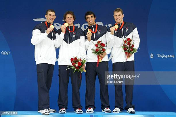Michael Phelps, Ryan Lochte, Ricky Berens and Peter Vanderkaay of the United States pose with the gold medal on the podium during the medal ceremony...