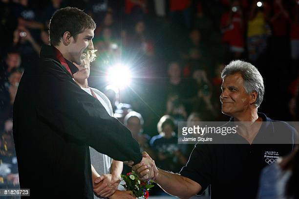 Michael Phelps shakes hands with legendary swimmer Mark Spitz during the awards ceremony for the 200 meter individual medley during the U.S. Swimming...