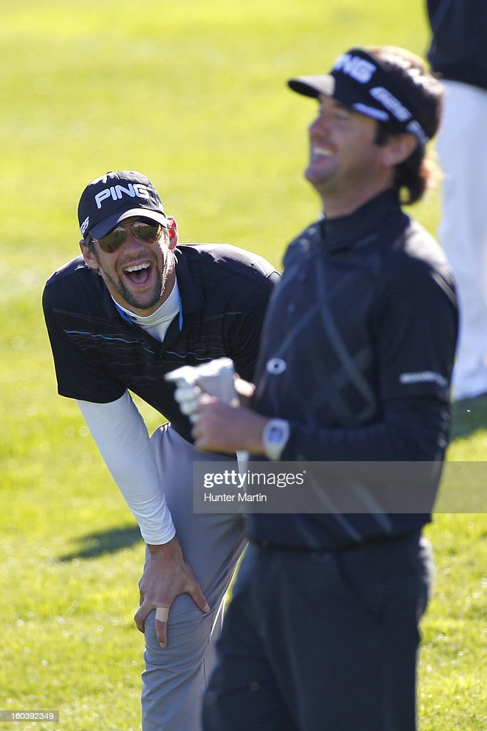 Michael Phelps shares a laugh with Bubba Watson on the 18th green during the Wednesday Pro-Am of the Waste Management Phoenix Open at TPC Scottsdale on January 30, 2013 in Scottsdale, Arizona.