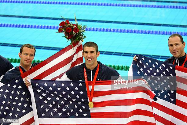 Michael Phelps stands between teammates Brendan Hansen and Jason Lezak of the United States after winning the gold medal in the Men's 4x100 Medley...